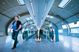 futuristic indoor walkway with blurred commuters poster
