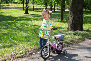 little girl with bicycle posing in park