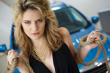 Young woman in the showroom with a new car with ropes