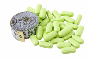 Isolated gray measure tape with green pills