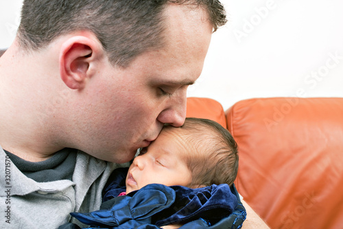Happy Father Kisses His Newborn Baby