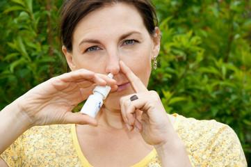 Junge Frau mit Nasenspray