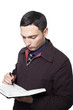 man in dark jacket and tie looking down and writing in planner