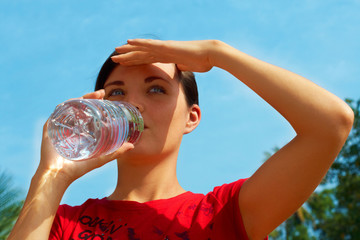 Beautiful young woman drinking the bottled pure water