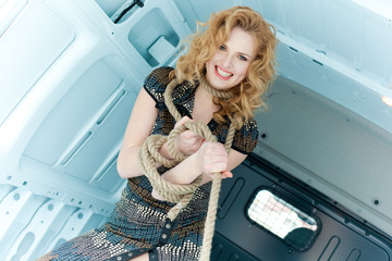 Pretty young woman in ropes in cargo van inside