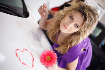 Young woman on hood of New car with flower and petals