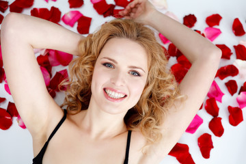Young woman lying back in rose petals on hood of New car