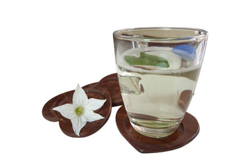 Glass of water and white flowers.