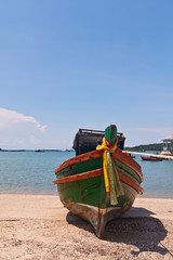 Wooden boat on the beach with blue sky from front vertical