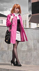 Beautiful ginger-haired woman in pink coat
