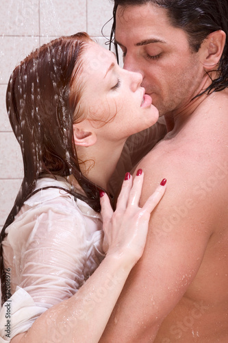 Man and woman in love are kissing in shower