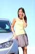 Young woman by car on mobile phone