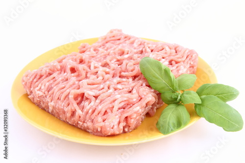 Raw minced meat on a plate decorated with basil