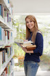 girl choosing book in library and smiling