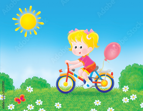 girl cycling through a field in summer day