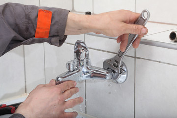 Plumber fixing water tap with spanner