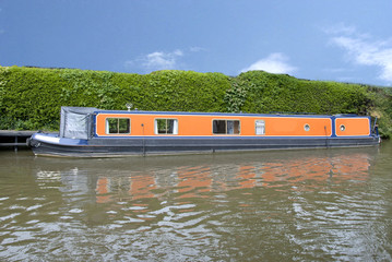 An Orange Narrowboat on a canal in Yorkshire under a blue sky