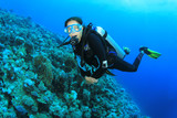Young Woman Scuba Diving over coral reef poster