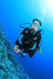Young Woman Scuba Diving in clear blue water poster