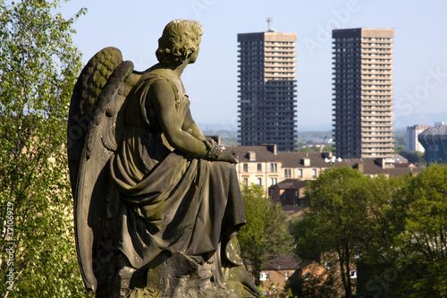 Urban angel contemplating high-rise tower blocks