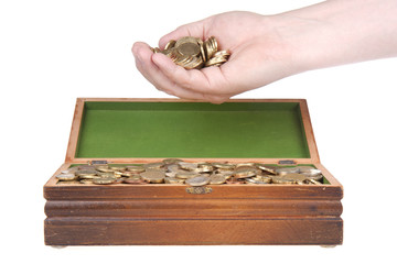 Hand full of coins over a treasure chest