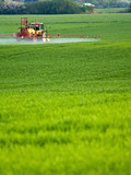 Tractor spraying a field on farm, agriculture