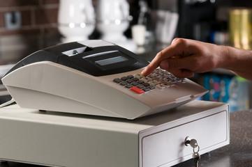 Closeup of a cashier's hand ringing cash register.