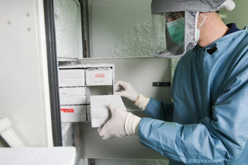 Scient placing a sample in the refrigerator