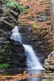 Autumn Waterfall in mountain with rocks and foliage