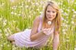 Mädchen mit Pusteblumen liegt auf der Wiese