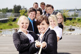 Lachende motivierte Mitarbeiter ziehen am Seil