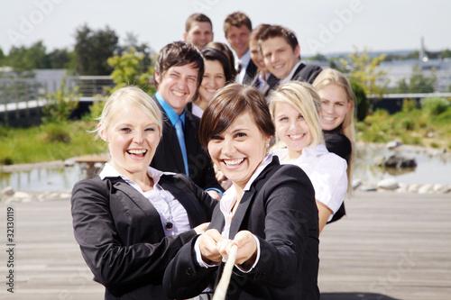 Leinwandbild Motiv Lachende motivierte Mitarbeiter ziehen am Seil