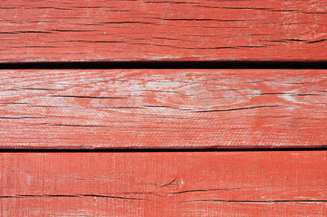Red painted threadbare wooden plank