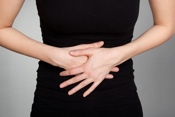 Young woman with stomach issues on grey