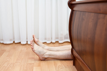 Bare hairy legs behind bed. Man lying on the floor in bedroom