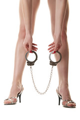 Female legs and hand holding handcuffs