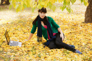 beautiful young girl with a laptop in a yellow autumn foliage