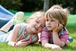 Kinder liegen auf dem Rasen