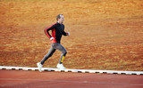 adult man running on athletics track