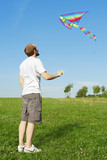 man in white shirt standing on summer meadow and flying multicol