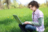 Girl with a laptop on the spring meadow