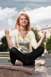 Ginger-haired woman meditating outdoor