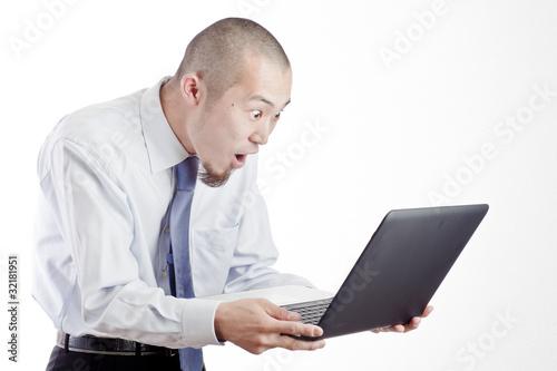 ノートパソコンを見て驚くビジネスマン