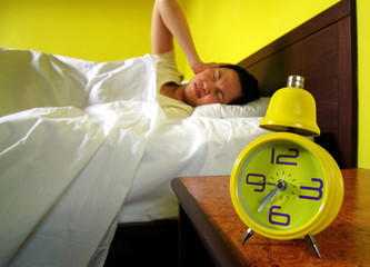 young woman and alarm clock in bedroom