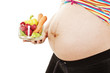 The young pregnant woman with vegetables on a white background
