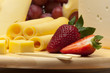A set of different cheeses, strawberry and grapes