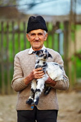 Old farmer with a baby goat