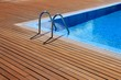 blue swimming pool with teak wood flooring - 32194946