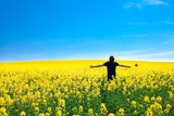 man with pinwheel standing in a field of yellow rape against the