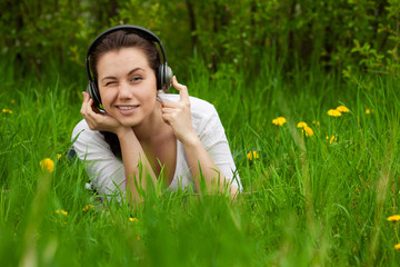 winking girl with headphones lying on the grass